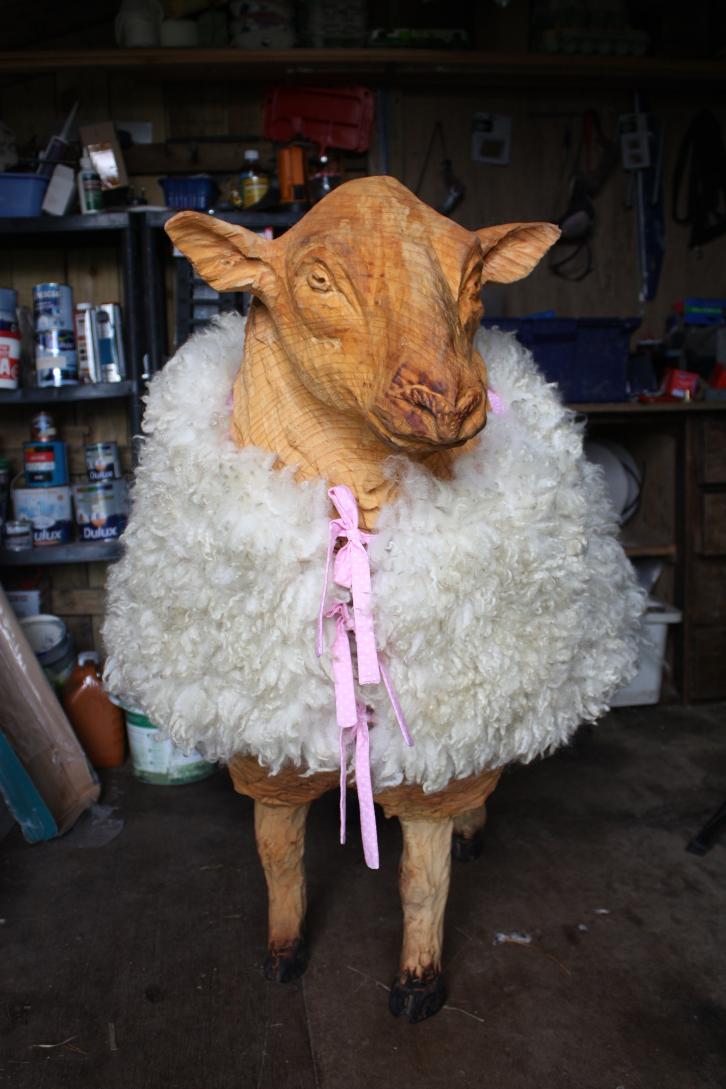 chainsaw carved sheep wearing jacket